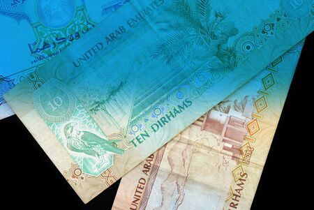 UAE dirham currency notes close up. Money background blue color toned