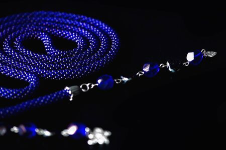 Long open necklace (lariat) blue color on a dark background close up
