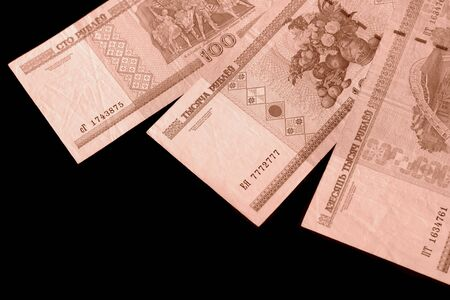 Outdated Belarusian rubles on black background close up brown color toned