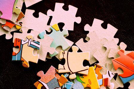 Children's puzzles on a dark surface close-up, brown color toned Banco de Imagens - 128429037