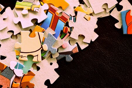 Children's puzzles on a dark surface close-up, brown color toned Banco de Imagens - 128429093