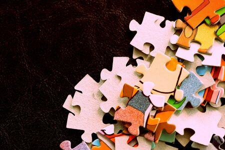 Children's puzzles on a dark surface close-up, brown color toned Banco de Imagens - 128429161
