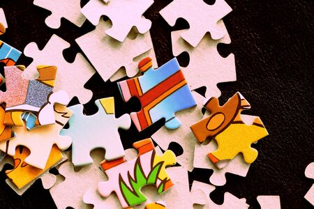 Childrens puzzles on a dark surface close-up, brown color toned