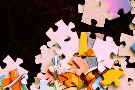 Children's puzzles on a dark surface close-up, brown color toned Banco de Imagens - 128475470