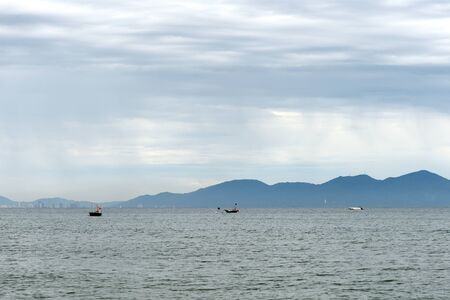 Seascape on the coast of Vietnam with a view of the mountains, boats and the city of Da Nang. Hoi An, Vietnam