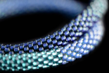 Fragment of a blue beaded necklace on a dark background close up