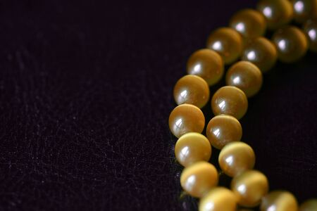 Yellow necklace of stone beads (cats eye) on a dark background close-up