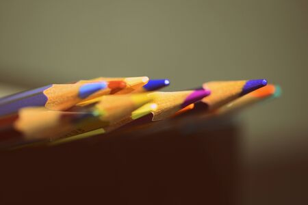 Colored pencils on a dark background close up. Retro style Stock Photo