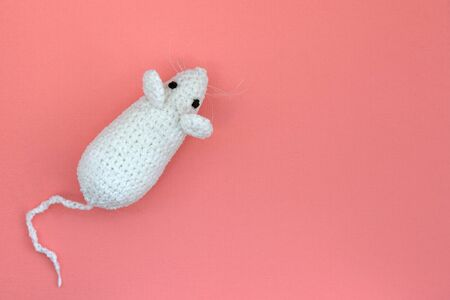 White crocheted rat on a pink background. Mouse symbol 2020 new year. Top view, copy space