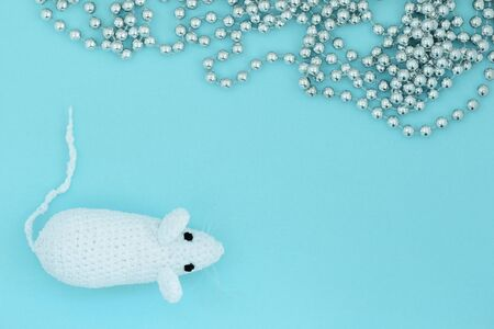 White crocheted rat on a blue background with silver christmas decoration. Mouse symbol 2020 new year. Top view, copy space