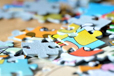 Colorful children puzzles on wooden background close-up