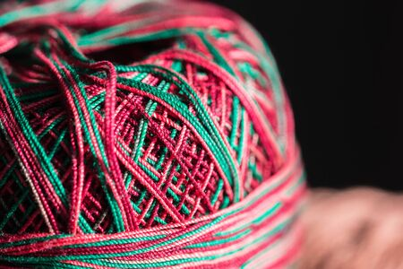Colored skeins of yarn lit by the sun close-up