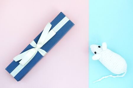 White crocheted rat and blue gift box on a paper background. Mouse symbol 2020 new year. Top view, copy space