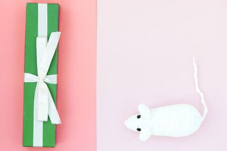 White crocheted rat and green gift box on a paper background. Mouse symbol 2020 new year. Top view, copy space