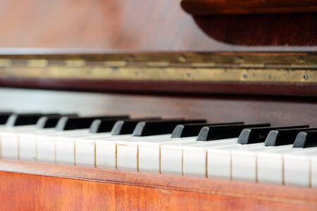 Old brown piano close-up. The keys of an old vintage piano