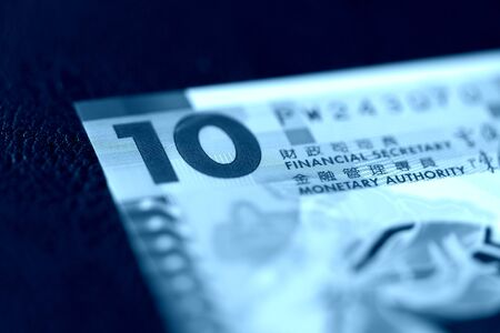 Ten Hong Kong dollars bill on a dark background close-up. Blue color toned