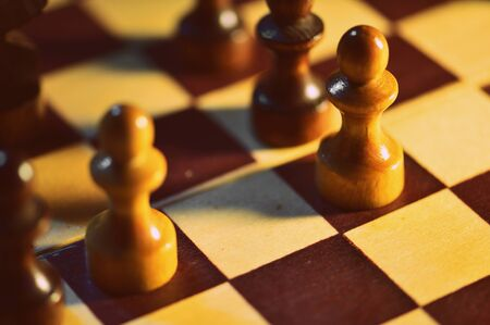 Chess figures on a wooden chessboard close up, retro style Stockfoto
