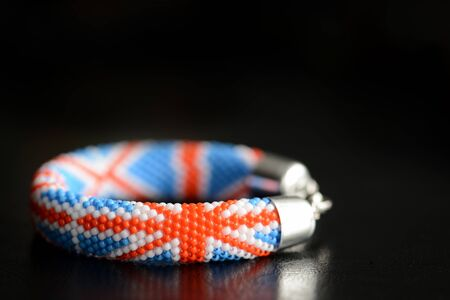 Bead croxhet bracelet with United Kingdom flag on a dark background close up
