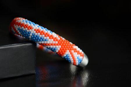 Bead croxhet bracelet with United Kingdom flag on a dark background close up