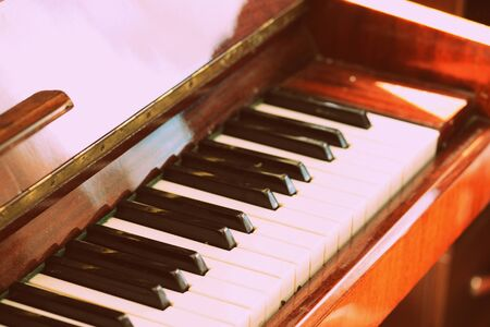 Old vintage piano brown color close-up. Retro style