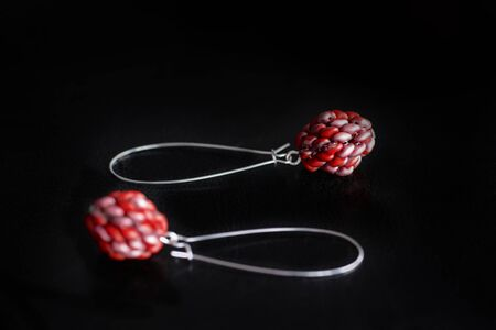 Red dangle earrings made of superduo beads on a dark background close-up Stok Fotoğraf