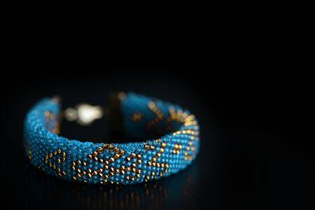 Beaded bracelet blue color with golden pattern on a dark background close up Stok Fotoğraf
