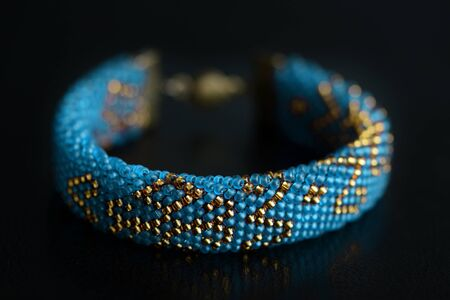 Beaded bracelet blue color with golden pattern on a dark background close up