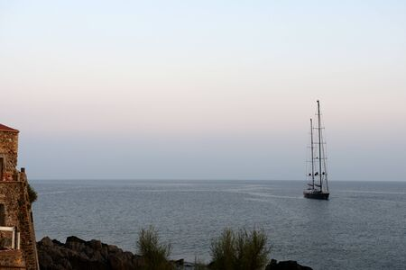 Seascape in the early morning with a yacht off the coast of Sicily. Cefalu, Italy Banco de Imagens