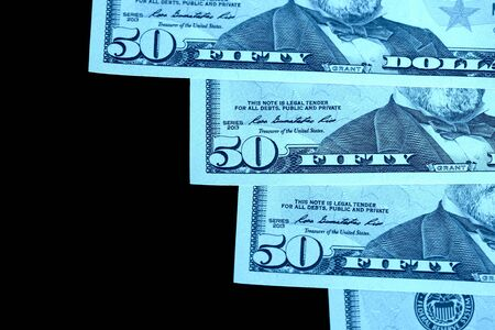 Fifty dollars banknotes isolated on black background close-up. Blue color toning