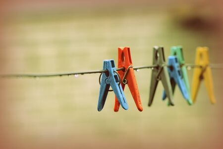 Plastic clothespins on wet wire after rain in the backyard close-up. Retro style