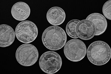 Thai Baht coins on a dark background close-up, black and white Imagens
