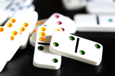 White domino scattered on a black background close-up