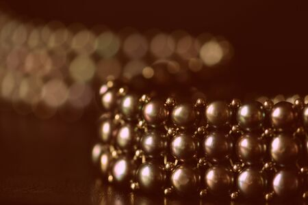 Black pearl necklace on a dark background close up. Retro style toned