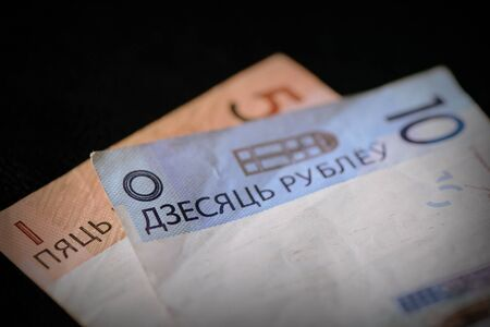 Two obsolete Belarusian banknotes of five and ten rubles on a dark background close-up. Retro style
