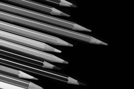 A pack of pencils on a dark background close up. Black and white