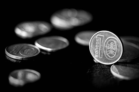 Belarusian coins scattered on a dark surface close up. Monochrome money background 스톡 콘텐츠