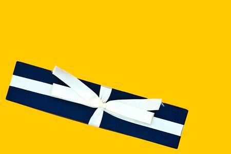 Blue gift box with a beige ribbon on a bright yellow background. Top view, copy space
