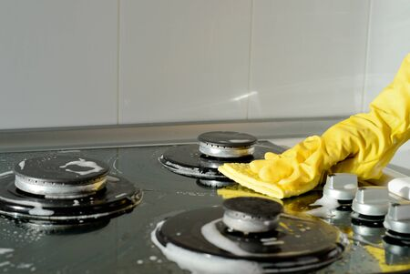 A hand in a yellow rubber glove washes a gas stove on a sunny day. Kitchen cleaning