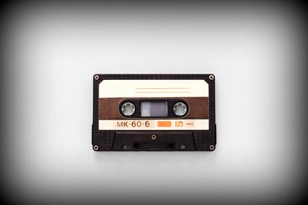 Audio tape cassette on a gray background close-up, top view. Old Technology Concept
