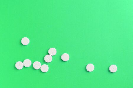White pills scattered on a green surface.