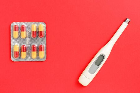 Thermometer and silver blister with pills on a red background.
