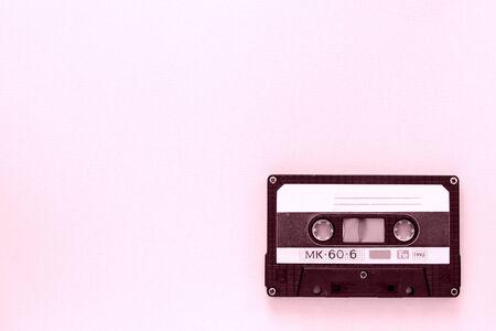 Gros plan sur une vieille cassette audio. Ancien concept de technologie. Couleur rose tonique
