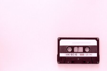 Old audio tape cassette close-up. Old technology concept. Pink color toned Фото со стока