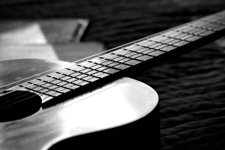 A fragment of an acoustic guitar lit by the sun. Black and white Banco de Imagens