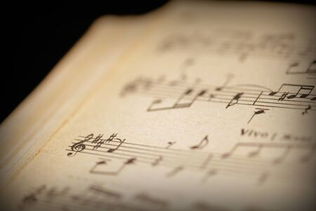 Fragment of a page from an old musical notebook on a dark surface close-up. Music background retro style toned Reklamní fotografie