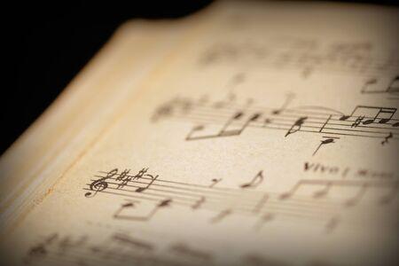Frammento di una pagina di un vecchio taccuino musicale su un primo piano di una superficie scura. Musica di sottofondo in stile retrò tonica Archivio Fotografico