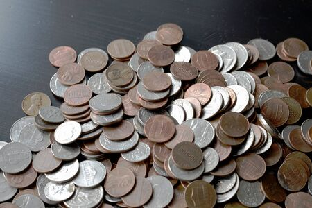 A pile of American cents on an old black wooden surface close-up. Money background