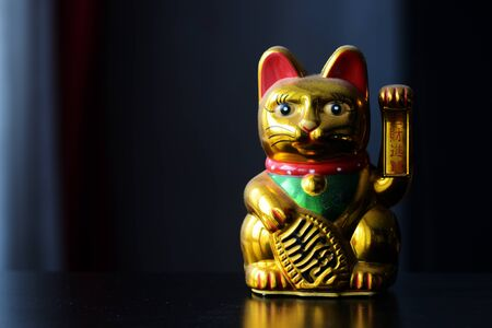 Golden Maneki Neko, the Lucky Cat, covered with dust. The concept of time and expectation of good luck