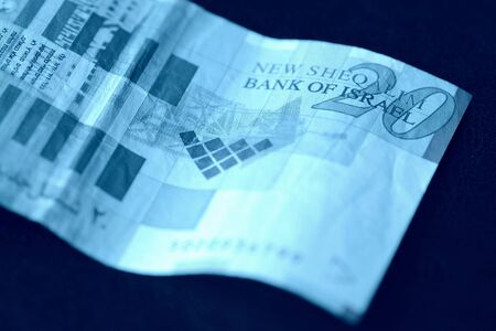 Twenty shekels banknote on a dark background close-up. Money background blue color toned