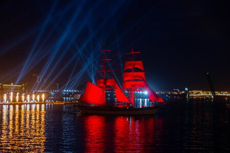 Beautiful ship with red sails on the night river. Scarlet Sails - a wonderful romantic performance on the Neva River in the city of St. Petersburg, Russia